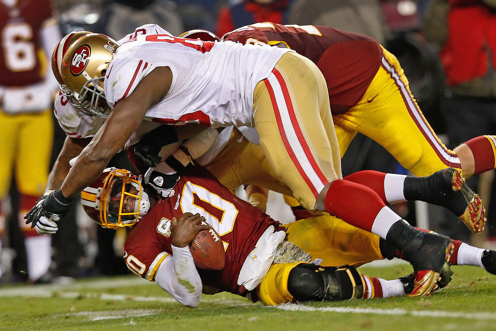 . Washington Redskins quarterback Robert Griffin III is knocked to the turf by San Francisco 49ers tight end Demarcus Dobbs, front, and another defender during the second half of an NFL football game in Landover, Md., Monday, Nov. 25, 2013. The 49ers deafeted the Redskins 27-6. (AP Photo/Alex Brandon)