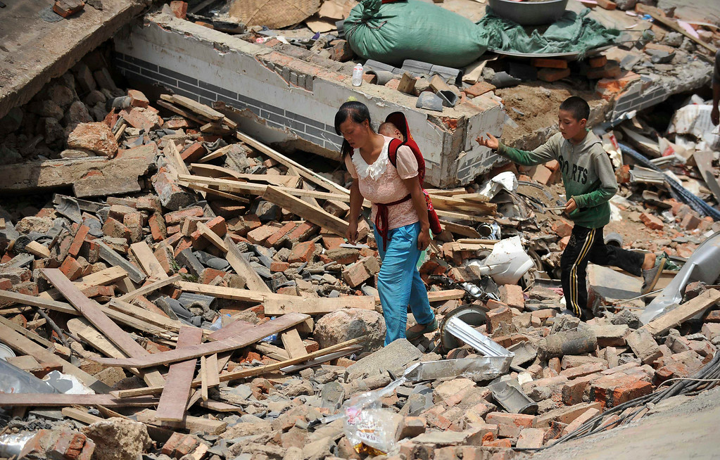 . In this photo provided by China\'s Xinhua News Agency, people walk past collapsed houses in the quake-hit Longtoushan township of Ludian county, southwest China\'s Yunnan Province, Tuesday, Aug. 5, 2014.   (AP Photo/Xinhua, Xue Yubin)  NO SALES