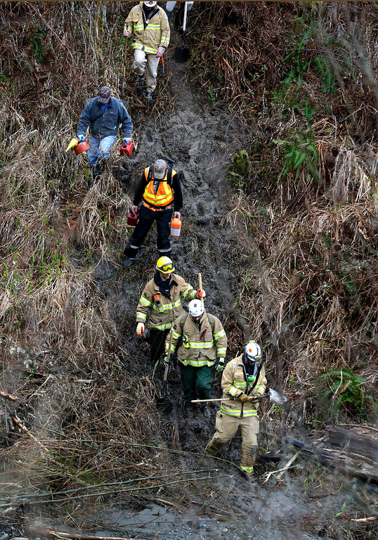 . Volunteers and firefighters with chainsaws and hand tools hike down a rugged path toward the scene of a deadly mudslide, Tuesday, March 25, 2014, in Oso, Wash.(AP Photo/Elaine Thompson)