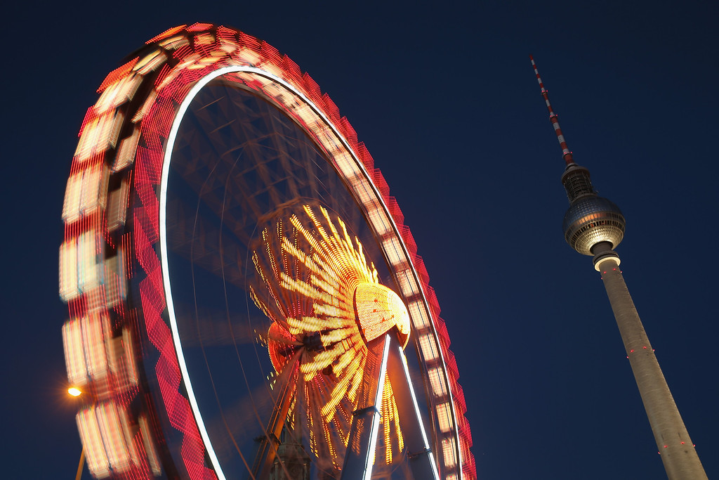 . An illuminated ferris wheel spins near the broadcast tower at Alexanderplatz square at a Christmas market on November 26, 0213 in Berlin, Germany.   (Photo by Sean Gallup/Getty Images)