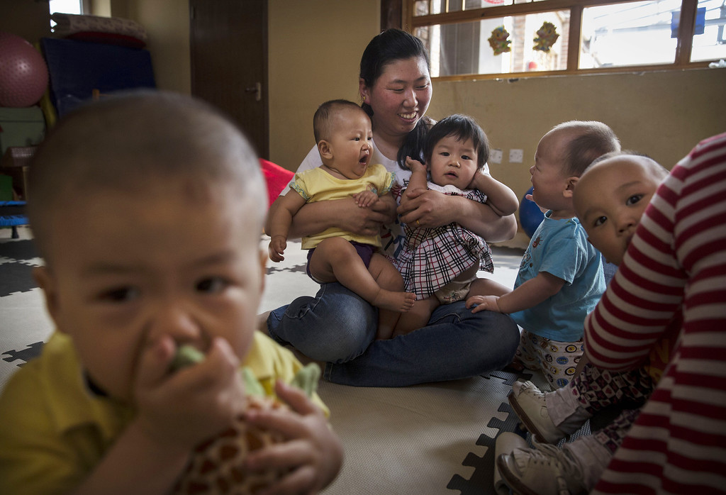. A Chinese care worker holds orphaned children at a foster care center on April 2, 2014 in Beijing, China.  (Photo by Kevin Frayer/Getty Images)
