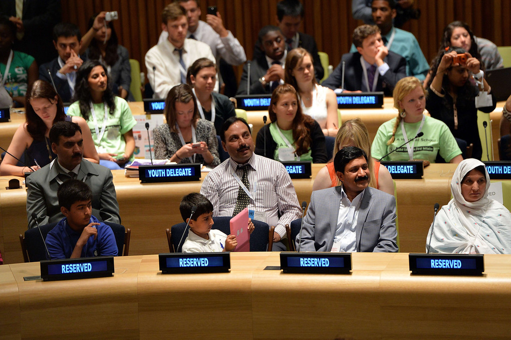 ". A brother (2nd L, front fow) of Pakistani student Malala Yousafzai, sitting with his family, takes photographs with a computer tablet as his sister speaks July 12, 2013 at United Nations headquarters in New York during the UN Youth Assembly. Yousafzai became a public figure when she was  shot by the Taliban while travelling to school last year in Pakistan -- targeted because of her committed  campaigning for the right of all girls to an education. The UN has declared July 12 ""Malala Day\"", which is also Yousafzai\'s birthday, and will host the  UN Youth Assembly.  STAN HONDA/AFP/Getty Images"