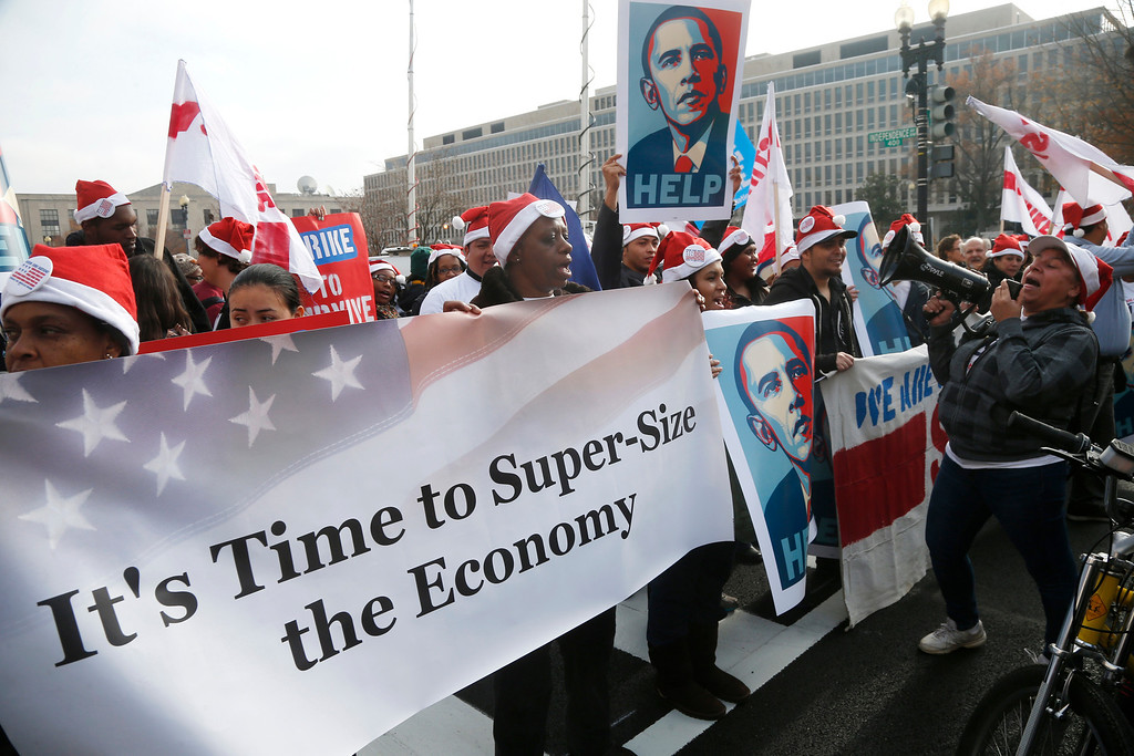 . Activists, holding posters of President Barack Obama, momentarily block Independence Avenue in Washington, Thursday, Dec. 5, 2013, as they protest the minimum wage outside a McDonald\'s restaurant at the Smithsonian\'s National Air and Space Museum in Washington, Thursday, Dec. 5, 2013.  (AP Photo/Charles Dharapak)