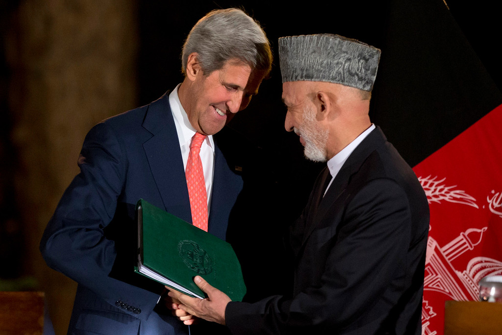 . U.S. Secretary of State John Kerry, left, leans in toward Afghan President Hamid Karzai as they say goodbye at the end of a news conference announcing a tentative agreement between the two countries at the Presidential Palace during Kerry\'s unannounced stop in Kabul, Afghanistan, on Saturday, Oct. 12, 2013, as a deadline approaches for a security deal about the future of U.S. troops in the country. (AP Photo/Jacquelyn Martin, Pool)