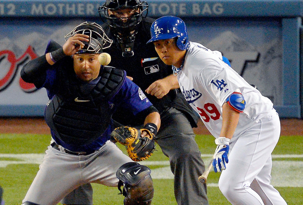 . Los Angeles Dodgers\' Ryu Hyun-jin, right, of South Korea, bunts into a double play as Colorado Rockies catcher Wilin Rosario watches during the second inning of their baseball game, Tuesday, April 30, 2013, in Los Angeles. (AP Photo/Mark J. Terrill)
