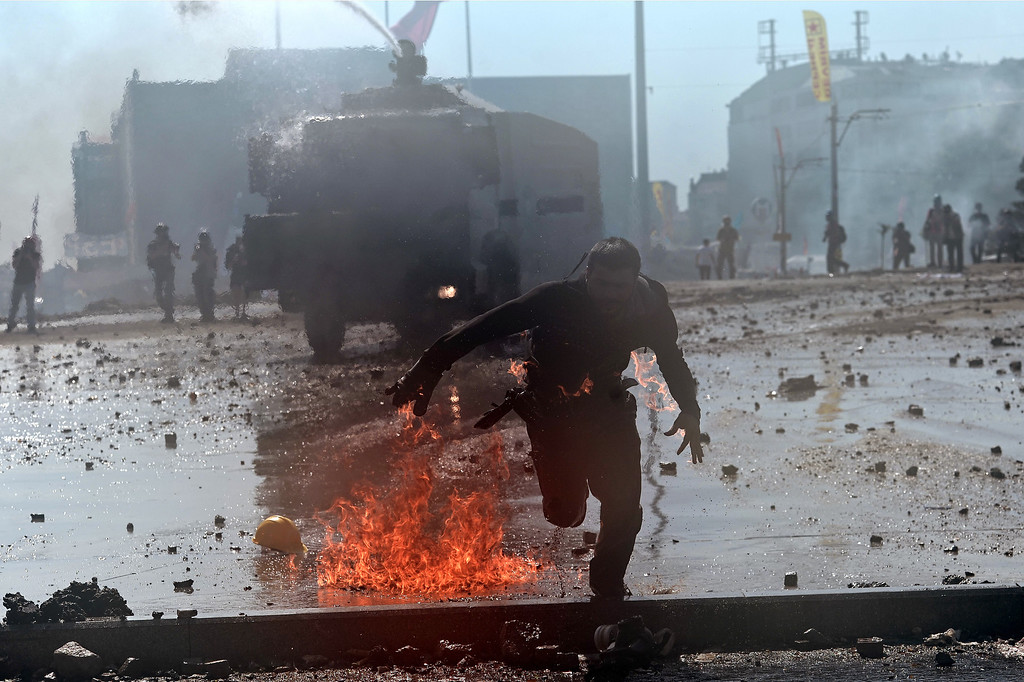 . A protester whose clothes are on fire runs away from riot police during clashes in Taksim square in Istanbul on June 11, 2013.  AFP PHOTO / ARIS MESSINIS/AFP/Getty Images