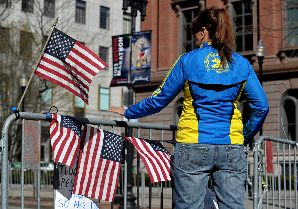 . A woman in a Boston Marathon runners jacket reaches out to touch a barrier at a makeshift memorial blocks from the finish line on April 17, 2013 in Boston, Massachusetts. Three people were reported killed after two explosions that struck near the finish line of the Boston Marathon on April 15. AFP PHOTO/Stan HONDA/AFP/Getty Images