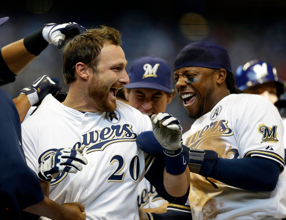 . Milwaukee Brewers\' Jonathan Lucroy, left, celebrates with Rickie Weeks, right, and other teammates after Lucroy\'s game-winning sacrifice fly against the Colorado Rockies in the 11th inning of an opening day baseball game on Monday, April 1, 2013, in Milwaukee. The Brewers won 5-4. (AP Photo/Jeffrey Phelps)