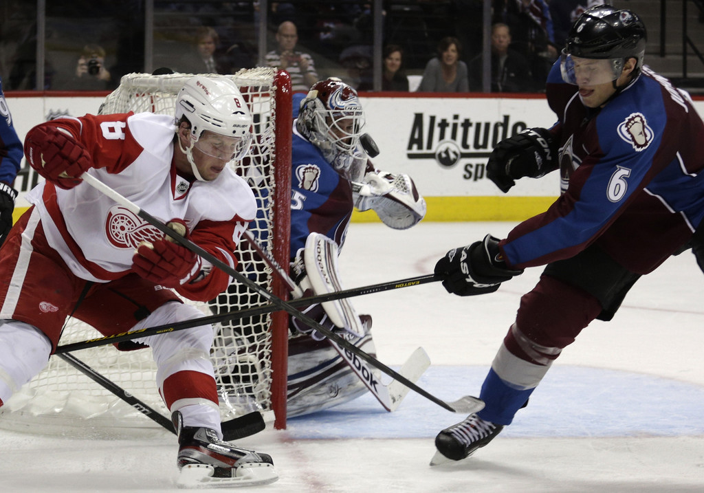 . Colorado Avalanche goalie Jean-Sebastien Giguere (35) watches the puck as Detroit Red Wings left wing Justin Abdelkader (8) and Colorado Avalanche defenseman Erik Johnson (6) swat at it in the second period of an NHL hockey game on Friday, April 5, 2013, in Denver. (AP Photo/Joe Mahoney)
