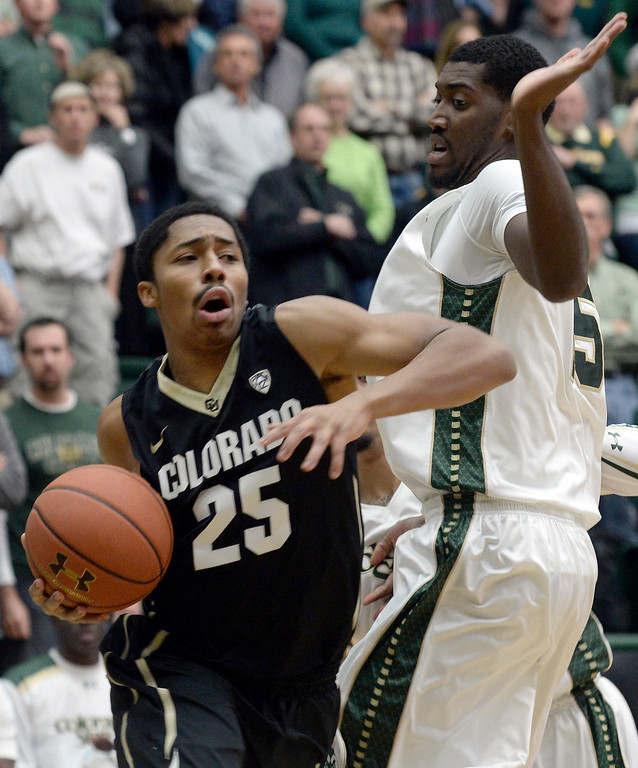 . Colorado\'s Spencer Dinwiddie drives past Gerson Santo during an NCAA game against CSU on Tuesday, Dec. 3, 2013, at the Moby Arena in Fort Collins. CU won the game 67-62.