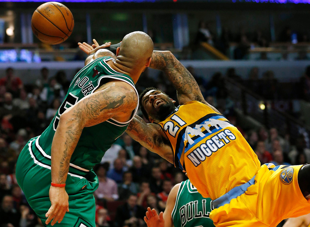 . Denver Nuggets\' Wilson Chandler (R) is blocked by Chicago Bulls\' Carlos Boozer during the first half of their NBA basketball game in Chicago, Illinois, March 18, 2013.  REUTERS/Jim Young