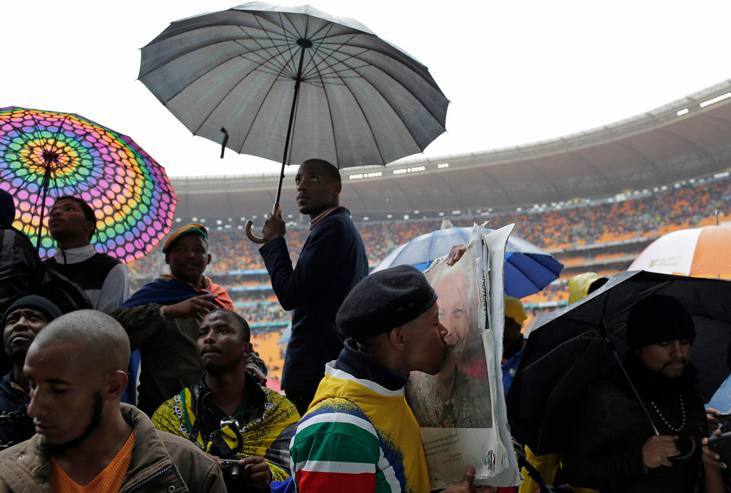 . A man kisses a portrait of Nelson Mandela as others shelter under umbrellas during the memorial service for former South African president Nelson Mandela at the FNB Stadium in Soweto, near Johannesburg, South Africa, Tuesday Dec. 10, 2013. (AP Photo/Bernat Armangue)