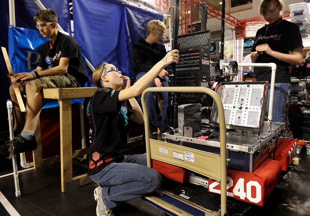 . DENVER, CO.- APRIL 6: Driver and team captain for the Denver School of Science and Technology, Allison Fisher, 14, (kneeling) works on the maintenance of the robot. The Colorado Regional FIRST Robotics Competition takes place in Magness Arena inside the Ritchie Center on the University of Denver campus. High School students from all over the state, region, and even a team from Mexico, participate in a high-tech spectator sporting event (this year the teams used frisbees) using specially engineered robots that are maneuvered by human drivers using computers and joy sticks.(Photo By Kathryn Scott Osler/The Denver Post)