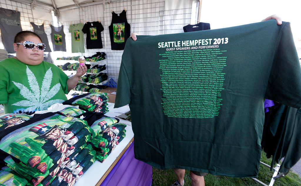 . A customer holds up a tee shirt for sale at the first day of Hempfest, Friday, Aug. 16, 2013, in Seattle. Thousands packed the Seattle waterfront park for the opening of a three-day marijuana festival ó an event that is part party, part protest and part victory celebration after the legalization of pot in Washington and Colorado last fall. Hempfest was expected to draw as many as 85,000 people per day. (AP Photo/Elaine Thompson)
