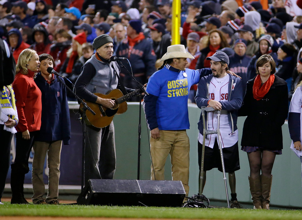 """. James Taylor sings \""""God Bless America\"""" alongside Carlos Arredondo, center, and Boston Marathon bombing survivor Jeff Bauman, second from right, during the seventh inning stretch of Game 2 of baseball\'s World Series between the Boston Red Sox and the St. Louis Cardinals Thursday, Oct. 24, 2013, in Boston. (AP Photo/Matt Slocum)"""