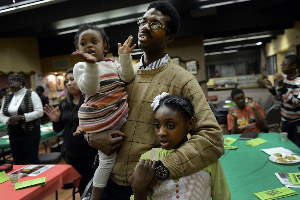 . Vincent Turner and his daughters Shepsira, 3, left, and Senbi, 8, sing a spiritual song during a Kwanzaa Celebration at the Zion Senior Center in Denver, CO, Saturday December, 29, 2012. The event highlighted the 150th anniversary of the Emancipation Proclamation with a theatrical performance depicting an enslaved family on Watch Night or Freedom\'s Eve, December 31, 1862. During the performance the family read the proclamation in anticipation of their coming freedom on New Years day, 1863. Craig F. Walker, The Denver Post