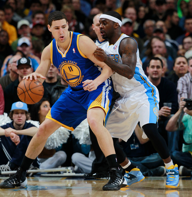 . Golden State Warriors guard Klay Thompson, left, works ball inside for a shot as Denver Nuggets guard Ty Lawson covers in the fourth quarter of the Warriors\' 89-81 victory in an NBA basketball game in Denver, Monday, Dec. 23, 2013. (AP Photo/David Zalubowski)